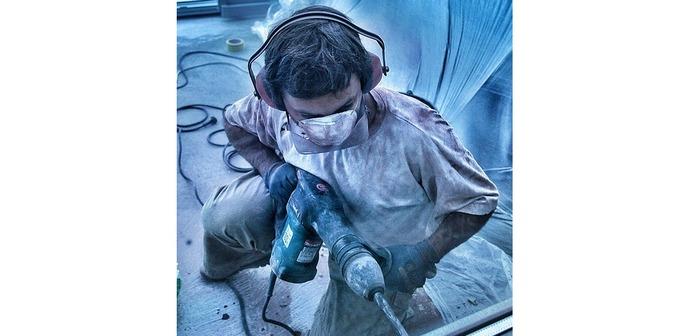 Человек с перфоратором делает ремонт